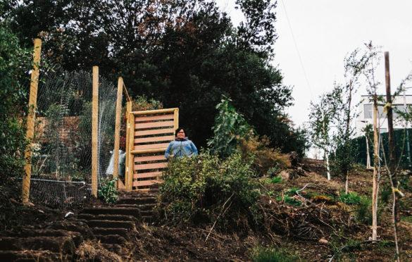 Miriam Meza posa fuera de su casa que colinda con el ascensor tipo funicular que conecta el cerro.