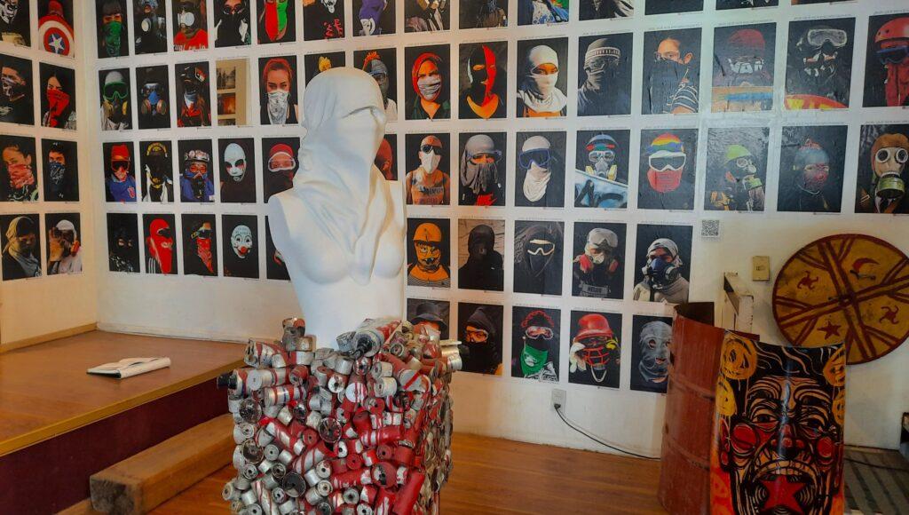 Sala del Museo del Estallido Social. Se aprecia una escultura y una pared repleta de fotos de los denominados