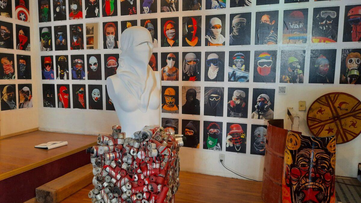 """Sala del Museo del Estallido Social. Se aprecia una escultura y una pared repleta de fotos de los denominados """"capuchas"""", manifestantes de las protestas de octubre que ocupaban la primera línea de la resistencia."""